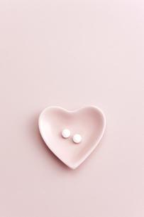 ハートの小皿に入れられた薬の写真素材 [FYI01620571]