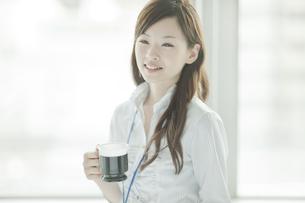 窓のそばに立ちコーヒーカップを持つビジネスウーマンの写真素材 [FYI01620598]