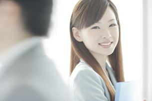 スーツ姿でファイルを持つ笑顔のビジネスウーマンの写真素材 [FYI01620600]