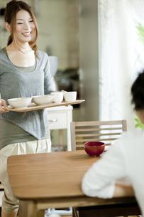 テーブルに食事を運ぶ日本人女性の写真素材 [FYI01620614]