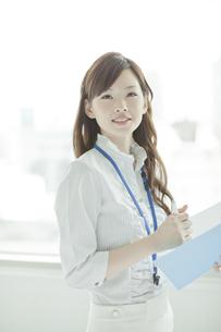 ファイルを持ち振り向く笑顔のビジネスウーマンの写真素材 [FYI01620625]