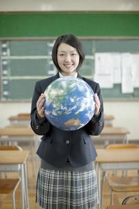 地球儀を持つ笑顔の女子校生の写真素材 [FYI01620626]