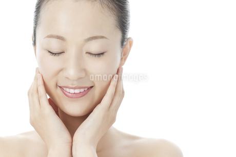 手を頬に添えて微笑む女性のスキンケアと美容イメージの写真素材 [FYI01620627]