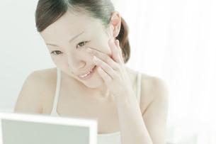 鏡の前で顔マッサージする女性スキンケアイメージの写真素材 [FYI01620635]