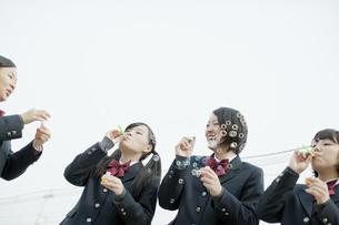 屋上でシャボン玉をする女子校生の写真素材 [FYI01620643]