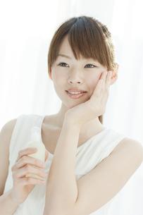 ローションを持つ若い女性の写真素材 [FYI01620657]