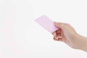ピンクのカードを持つ女性の手の写真素材 [FYI01620660]