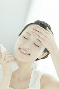 化粧水で顔にうるおいを与える女性 美容とスキンケアイメージの写真素材 [FYI01620669]