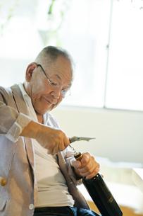 ワインの栓をぬくシニア男性の写真素材 [FYI01620670]