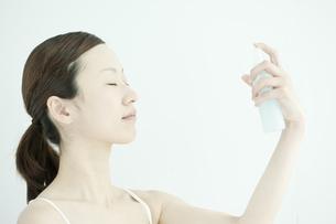 顔にスプレーする女性のスキンケアイメージの写真素材 [FYI01620671]
