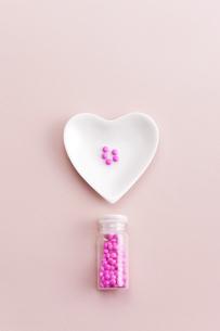 ハートの小皿に入れられた薬と薬瓶の写真素材 [FYI01620672]