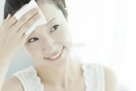 コットンを顔に置く女性 美容とスキンケアイメージの写真素材 [FYI01620678]