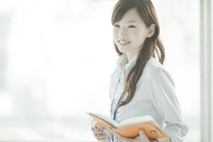 手帳と携帯電話を持つビジネスウーマンの写真素材 [FYI01620688]