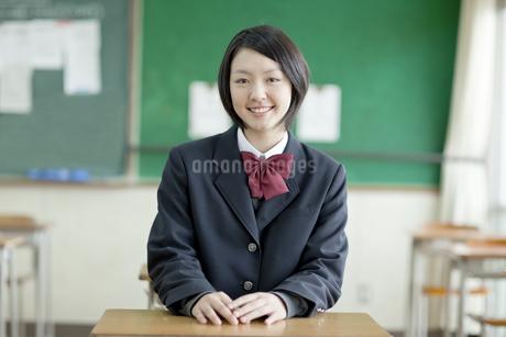 机に座る笑顔の女子校生の写真素材 [FYI01620689]