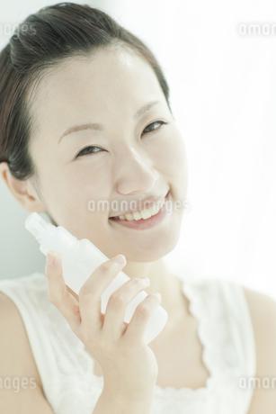 化粧水のボトルを持つ女性 美容とスキンケアイメージの写真素材 [FYI01620690]