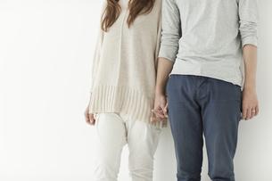 寄り添い手を繋いで立つ若い夫婦の写真素材 [FYI01620691]