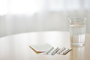 テーブルに置かれた薬と水の写真素材 [FYI01620697]
