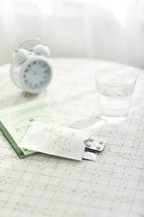 テーブルに置かれた薬と水の写真素材 [FYI01620701]