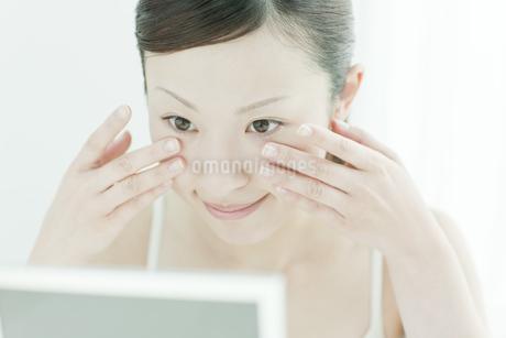 鏡の前で顔マッサージする女性スキンケアイメージの写真素材 [FYI01620702]