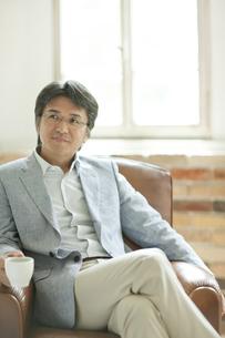 ソファーに座りコーヒーを飲むミドル男性の写真素材 [FYI01620726]