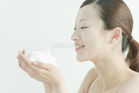 洗顔の泡を手にのせる若い女性スキンケアイメージの写真素材 [FYI01620733]