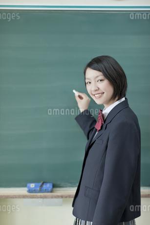 黒板の前でチョークを持つ笑顔の女子校生の写真素材 [FYI01620736]