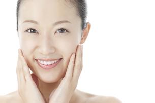 手を頬に添えて微笑む女性のスキンケアと美容イメージの写真素材 [FYI01620738]