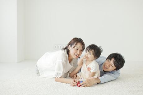 おすわりする赤ちゃんと寝転ぶ夫婦の写真素材 [FYI01620747]