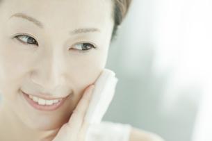 コットンを顔に置く女性 美容とスキンケアイメージの写真素材 [FYI01620750]
