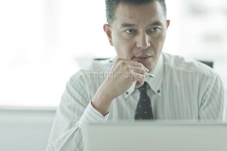 デスクで考えるビジネスマンの写真素材 [FYI01620762]