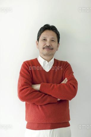 腕組みをして壁の前に立つシニア男性の写真素材 [FYI01620772]