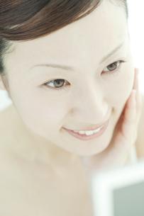 鏡の前で喜ぶ女性のスキンケアイメージの写真素材 [FYI01620773]