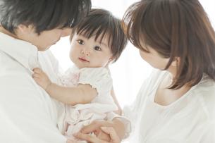 赤ちゃんを抱っこする父親と母親の写真素材 [FYI01620777]