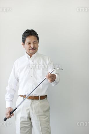壁の前に立ちゴルフクラブを持つシニア男性の写真素材 [FYI01620785]