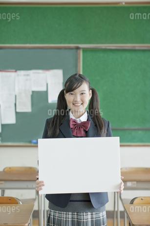 ホワイトボードを持つ笑顔の女子校生の写真素材 [FYI01620794]
