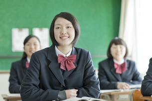 授業中先生の話を聞く笑顔の女子校生の写真素材 [FYI01620797]