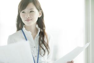 書類を持つ笑顔のビジネスウーマンの写真素材 [FYI01620800]
