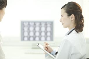 モニターの前で患者と話す女性医師の写真素材 [FYI01620803]