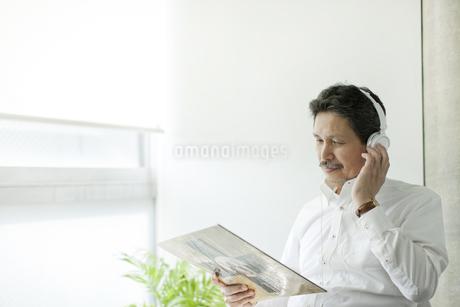 ジャケットを見ながら音楽を聴くシニア男性の写真素材 [FYI01620810]