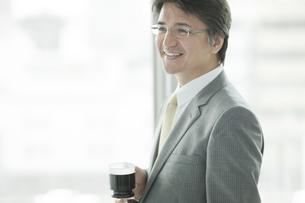 窓際に立ちコーヒーを飲む笑顔のビジネスマンの写真素材 [FYI01620820]