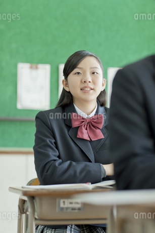 授業中先生の話を聞く笑顔の女子校生の写真素材 [FYI01620835]