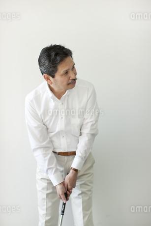 壁の前でゴルフの練習をするシニア男性の写真素材 [FYI01620842]