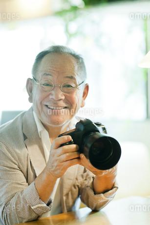 一眼レフカメラを持つシニア男性の写真素材 [FYI01620845]