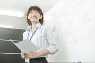 ホワイトボードの前で発言する女性社員の写真素材 [FYI01620846]