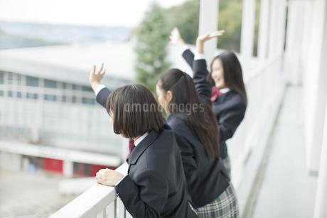 バルコニーから手を振る女子校生の写真素材 [FYI01620848]