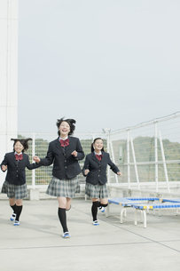 屋上を走る笑顔の女子校生の写真素材 [FYI01620864]