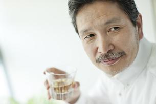 ウイスキーを飲み振り向くシニア男性の写真素材 [FYI01620870]
