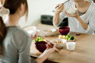 テーブルで和食を食べる若い夫婦の写真素材 [FYI01620879]