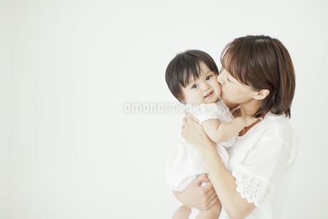 赤ちゃんを抱っこしてキスをする母親の写真素材 [FYI01620882]