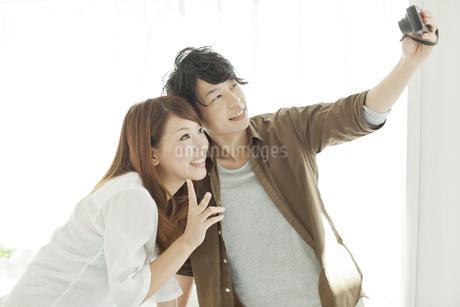 デジタルカメラで2人の写真を撮る男性の写真素材 [FYI01620887]